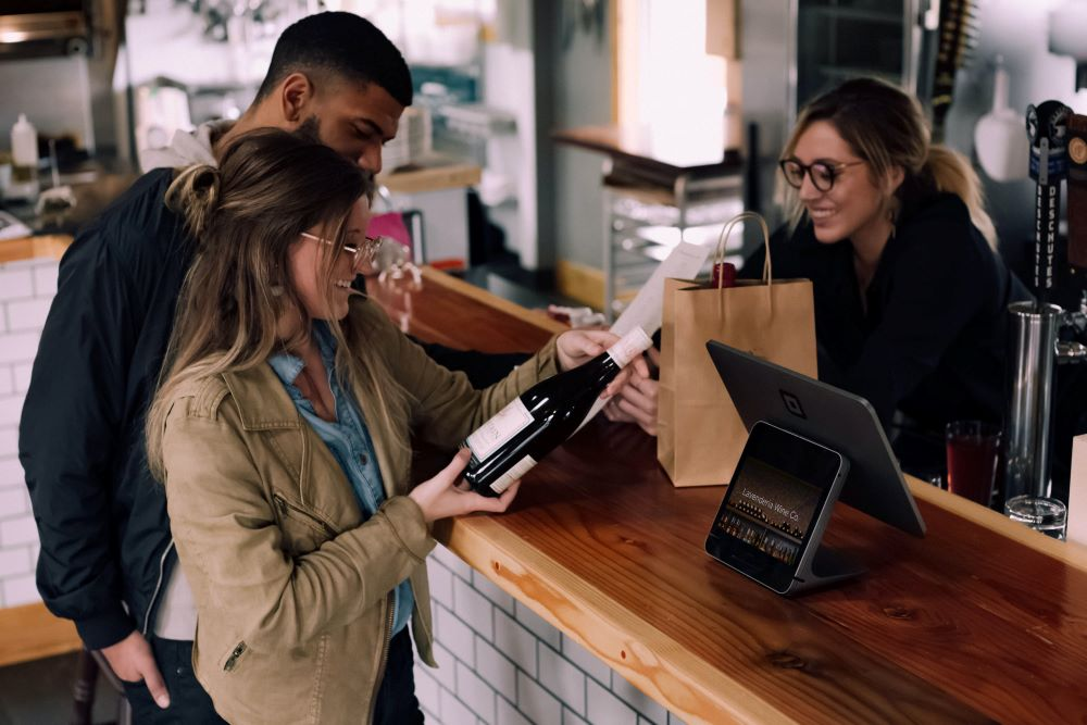 man and woman buying wine
