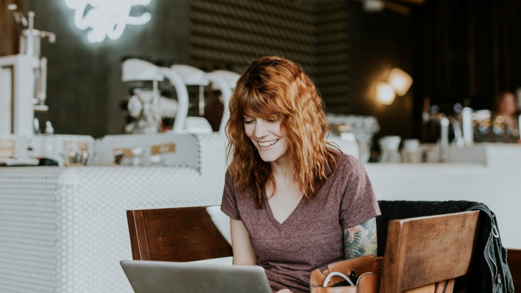 happy woman at cafe with laptop