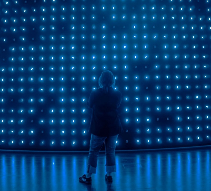 person standing on stage with blue lights