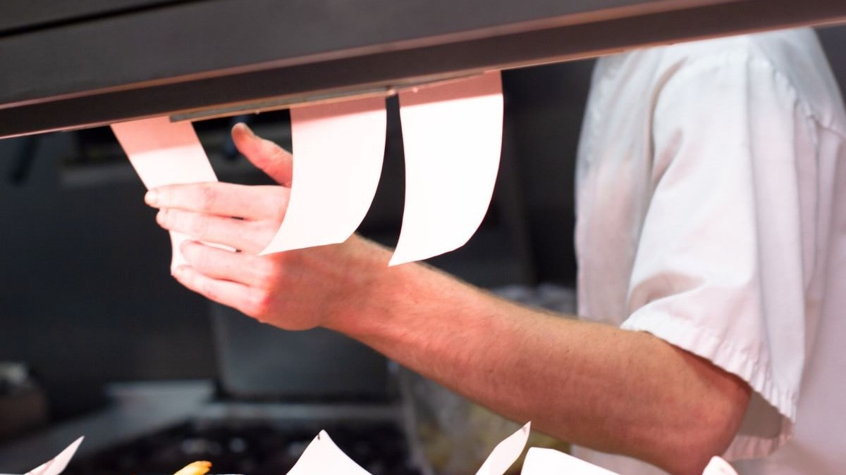 man takes order ticket at cafe grill