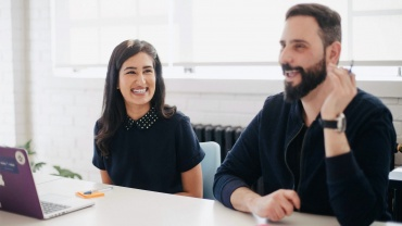 man and woman smiling in meeting discussion