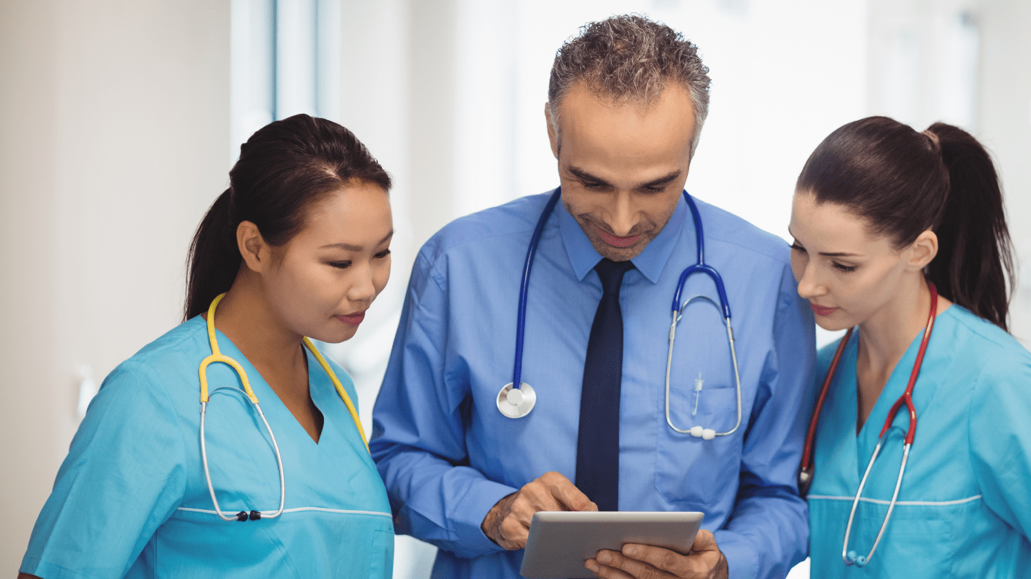 a doctor and two nurses check records on a tablet