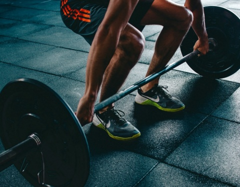 man at gym lifts barbell weight