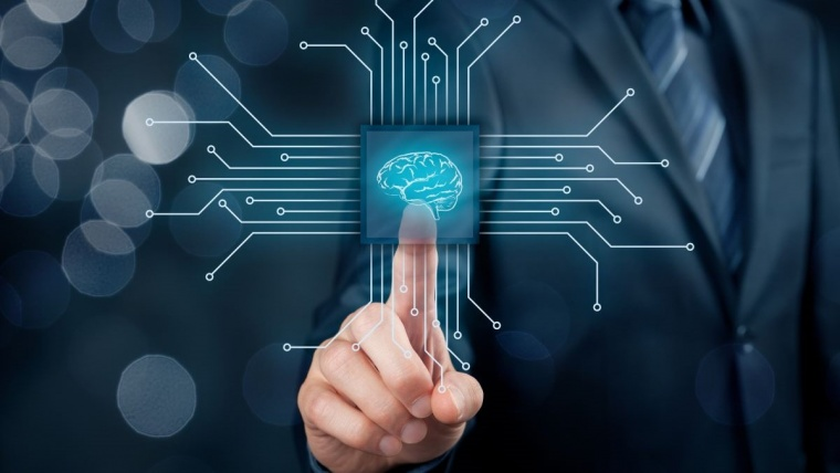 hand pointing at brain on a computer chip