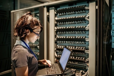 Woman standing with a laptop at datacenter